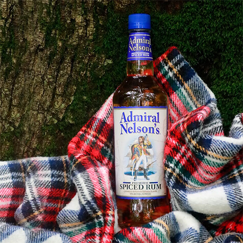 A bottle of Admiral Nelsons wrapped in a flannel blanket